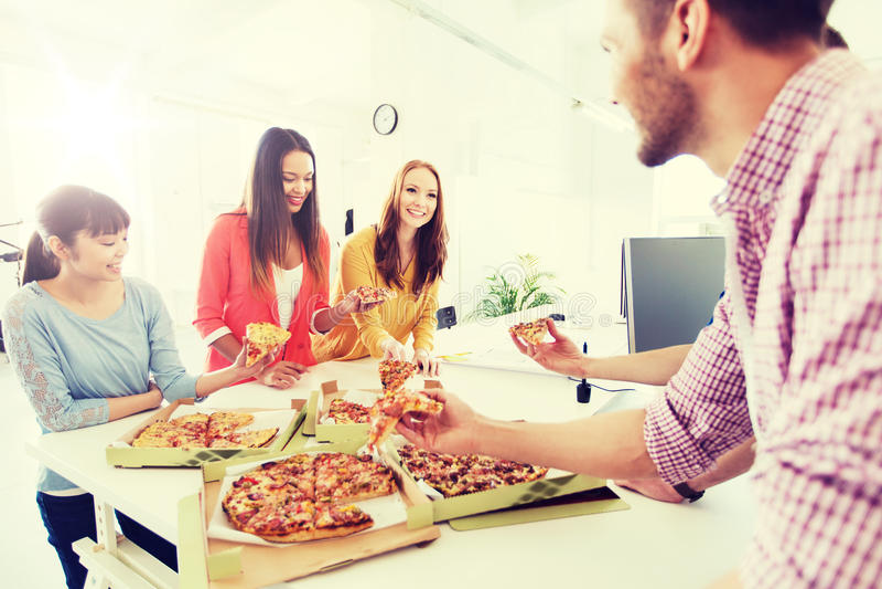 Equipe feliz do negócio que come a pizza no escritório fotografia de stock