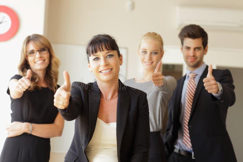 Equipe feliz do negócio que mostra os polegares acima imagem de stock