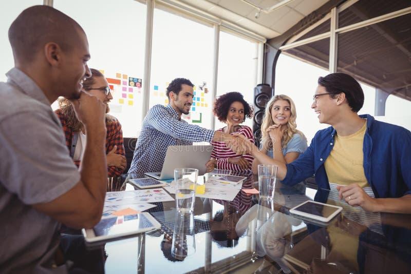 Equipe feliz do negócio que trabalha junto no escritório imagens de stock