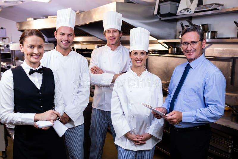 Equipe feliz do restaurante que está junto na cozinha comercial foto de stock