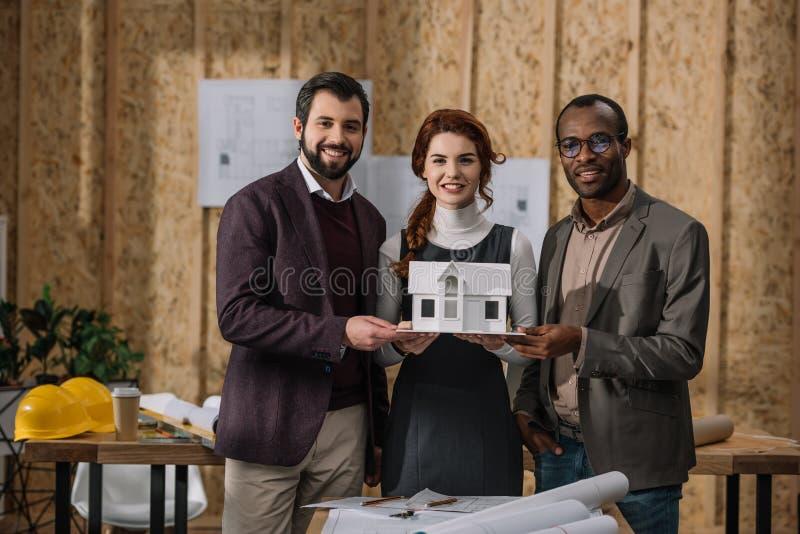 equipe feliz dos arquitetos que guardam o modelo diminuto da construção fotografia de stock royalty free
