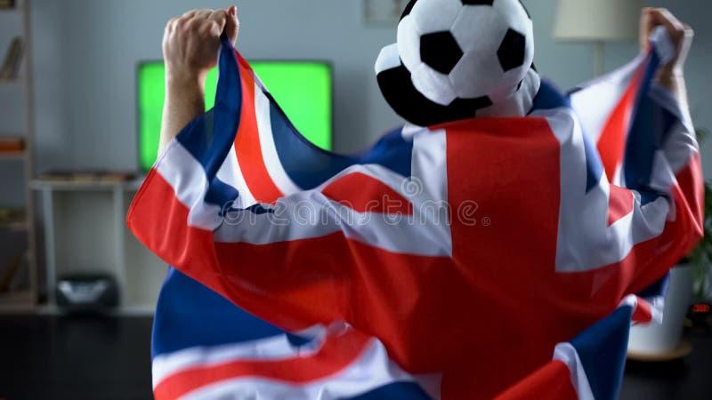 Equipe guardar a bandeira de Grâ Bretanha, jogo de futebol de observação do suporte na tevê em casa imagens de stock