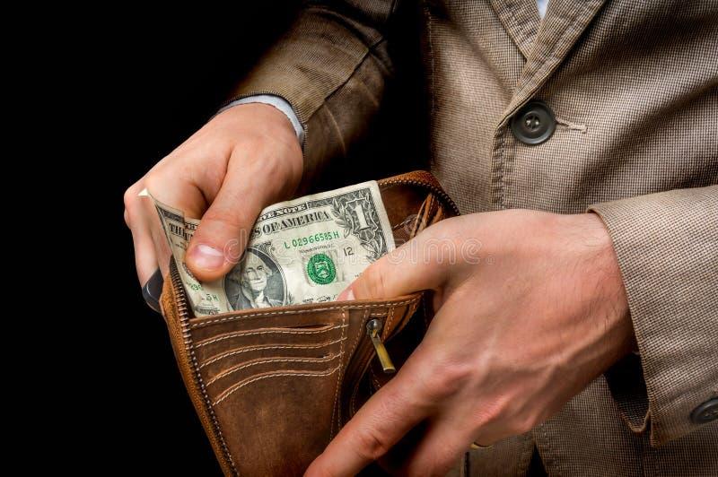 Equipe guardar a carteira de couro com somente um dólar para dentro imagens de stock royalty free