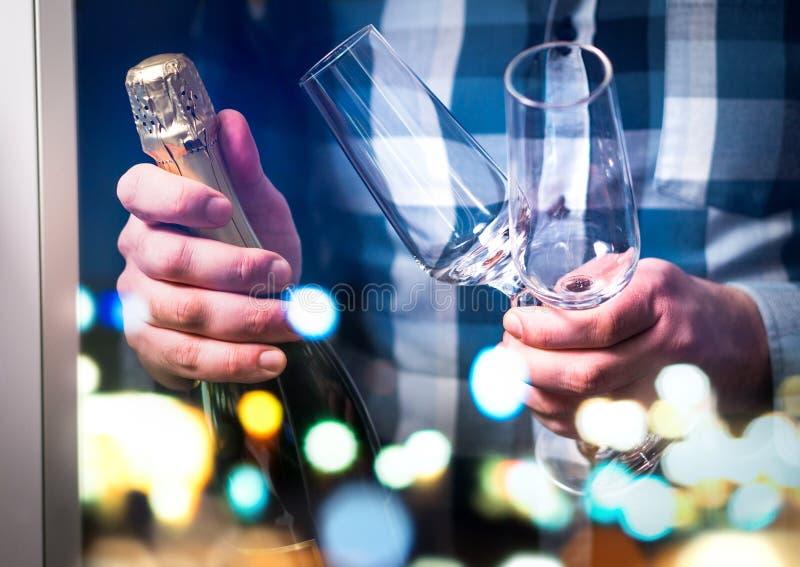 Equipe guardar a garrafa do champanhe ou o vinho espumante e os dois vidros fotografia de stock