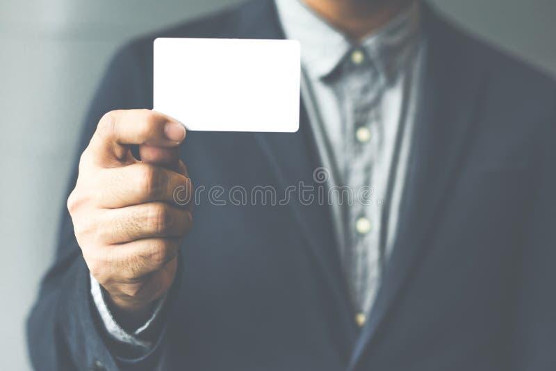 Equipe guardar o cartão branco, homem que veste a camisa azul e que mostra o cartão branco vazio Fundo borrado Mocku horizontal imagem de stock royalty free