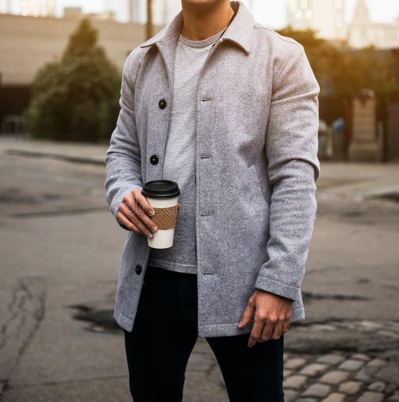 Equipe guardar o revestimento cinzento vestindo e a posição de veludo do copo de café na rua da cidade na maneira ao escritório imagem de stock