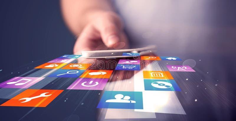 Equipe guardar o telefone esperto com ícones coloridos da aplicação foto de stock