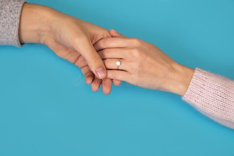 Equipe guardar o Valentim azul da história de amor da proposta do noivo da amiga do fundo das mãos da aliança de casamento fotos de stock