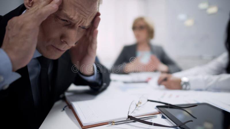 Equipe guardar sua cabeça, ataque da enxaqueca causado pelo esforço, exaustão no local de trabalho fotos de stock
