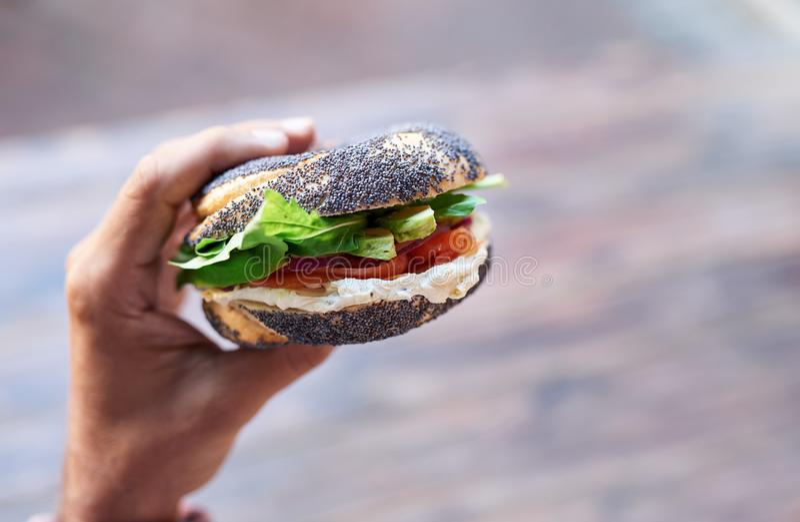 Equipe guardar um bagel delicioso do queijo creme e dos salmões fotos de stock royalty free