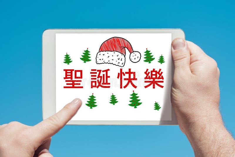 Equipe guardar um dispositivo da tabuleta com texto no ` chinês do Feliz Natal do ` e o toque da tela imagens de stock