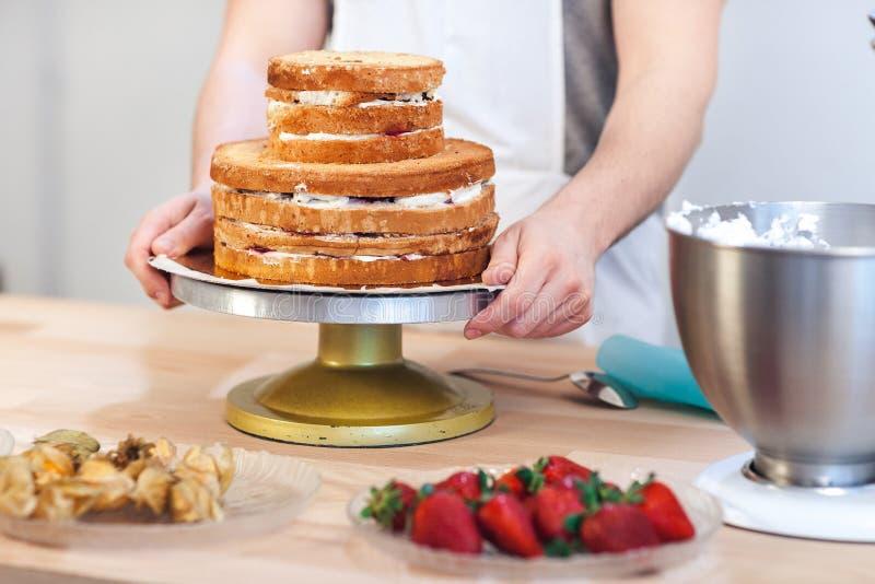 Equipe guardar um pedaço de bolo em suas mãos, preparando-se para decorar o bolo com fruto fotos de stock