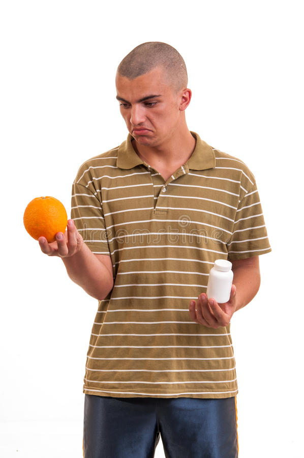 Equipe guardar uma laranja em uma mão e comprimidos em outra imagem de stock