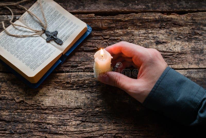 Equipe guardar uma vela na frente da Bíblia e da cruz imagens de stock