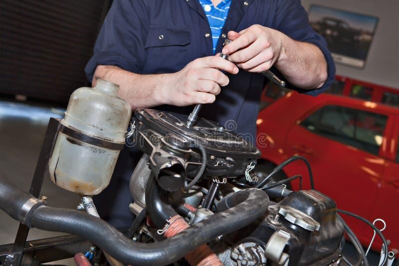 Equipe guardarar uma chave inglesa sobre um motor de automóveis imagens de stock royalty free