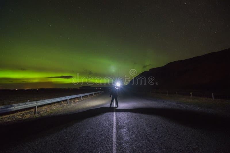 Equipe a iluminação acima de uma estrada sob Aurora Borealis em Islândia fotografia de stock