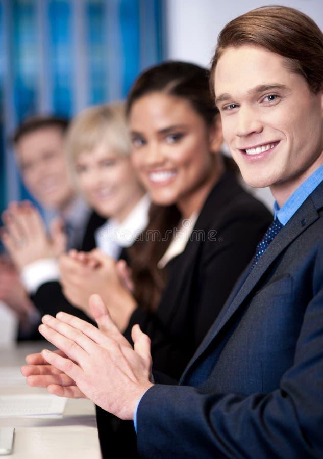Equipe incorporada que senta-se em seguido e que aplaude fotos de stock royalty free