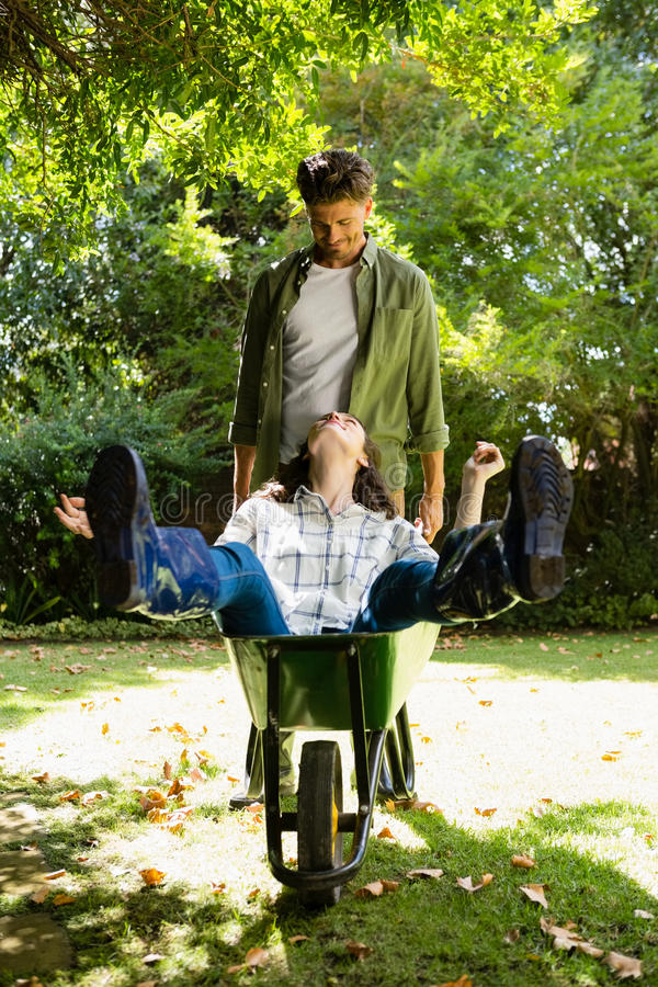 Equipe a interação com a mulher ao empurrar o carrinho de mão no jardim fotos de stock