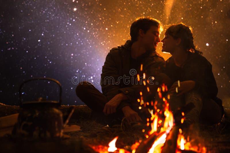 Equipe jogos guitarra e mulher sobre o fogo no fundo do céu estrelado imagens de stock royalty free