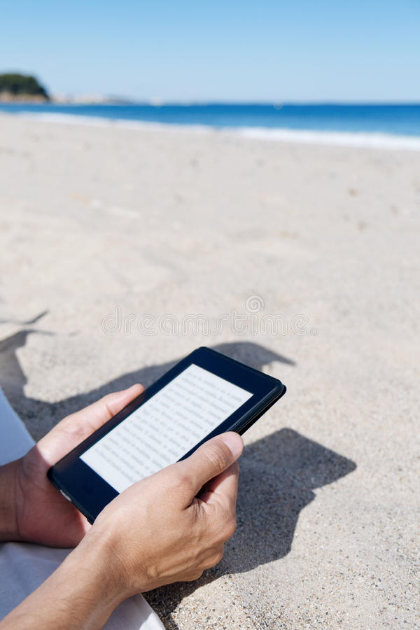 Equipe a leitura em uma tabuleta ou em um e-leitor na praia fotos de stock royalty free