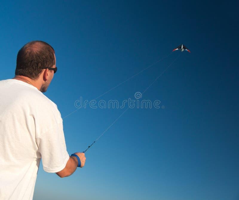 Equipe a liberação de um papagaio acima no ar no dia de verão ensolarado fotografia de stock