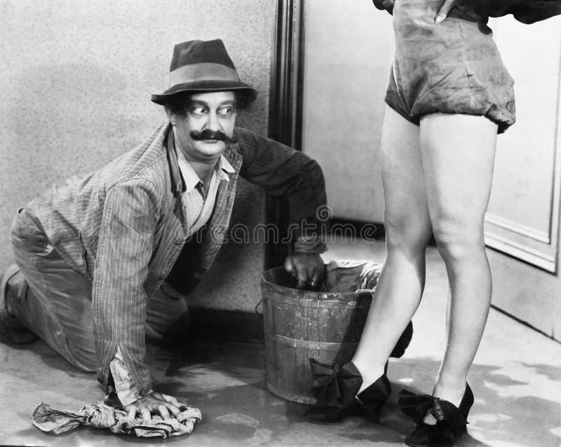 Equipe a limpeza do assoalho que olha os pés de uma mulher (todas as pessoas descritas não são umas vivas mais longo e nenhuma pr fotografia de stock royalty free