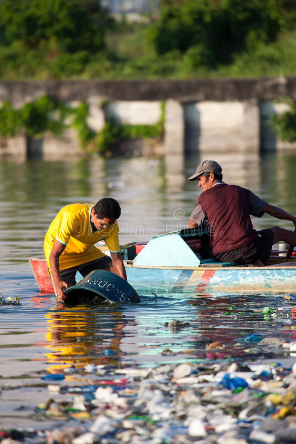 Equipe a limpeza para fora de sua cubeta no rio poluído imagem de stock royalty free