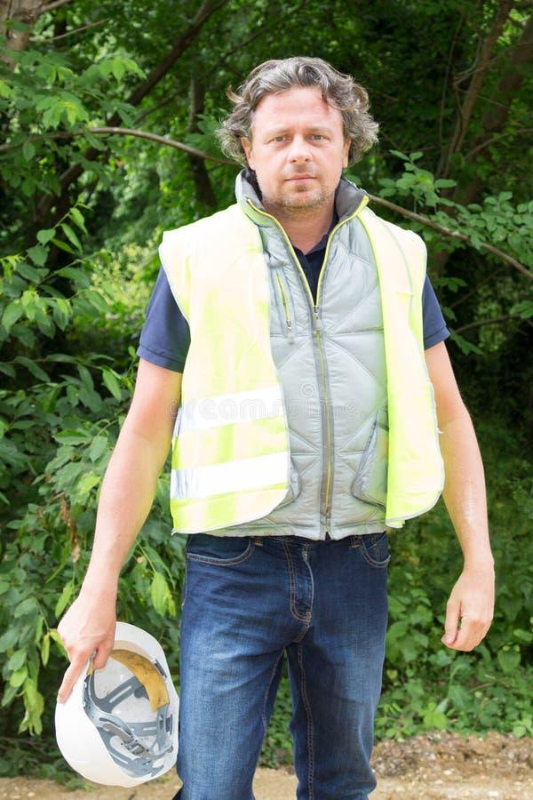 Equipe a máquina escavadora masculina do motorista do operador no terreno de construção da construção imagem de stock