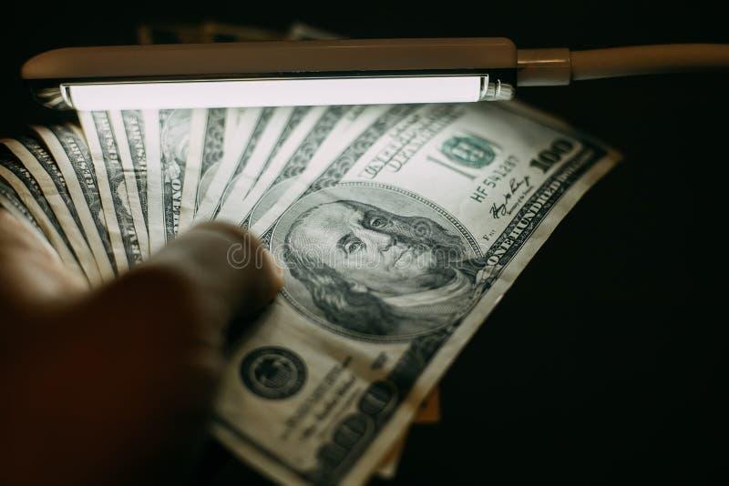 Equipe a mão com uma pilha de cem contas dos dólares americanos sobre a cédula fotografia de stock royalty free