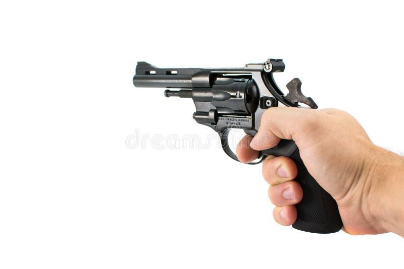 Equipe a mão do ` s que guarda a arma do revólver, isolada no fundo branco imagens de stock