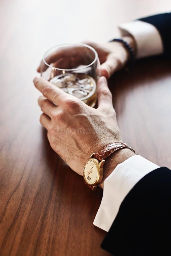 Equipe a mão do ` s que guarda um vidro do uísque imagem de stock royalty free