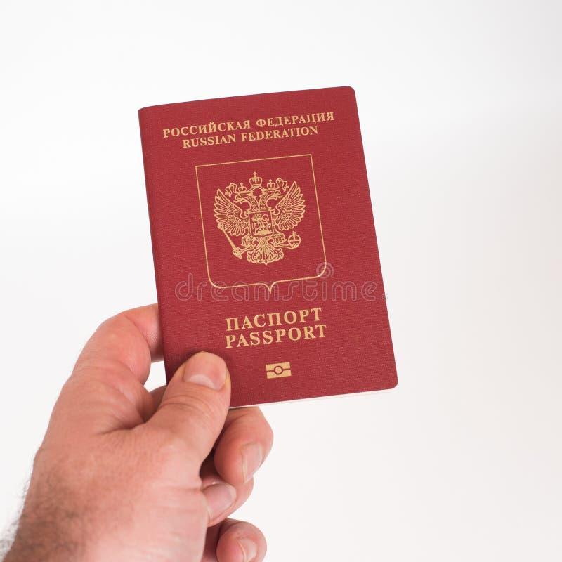 Equipe a mão do ` s que mantém o passaporte internacional do russo isolado no fundo branco fotografia de stock royalty free