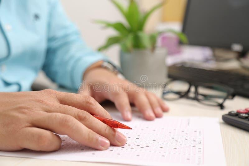 Equipe a mão na folha do OMR com pena Imagem do computador, do teclado, do potenciômetro de flor e dos vidros fotografia de stock