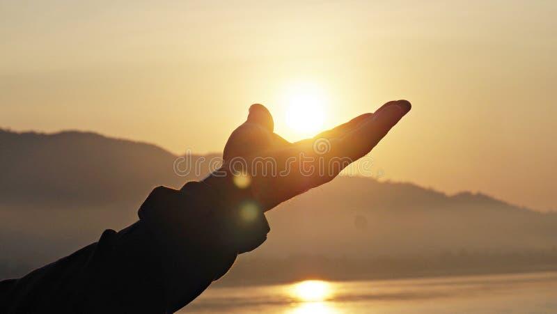 Equipe a mão que alcança ao sol na manhã imagem de stock royalty free