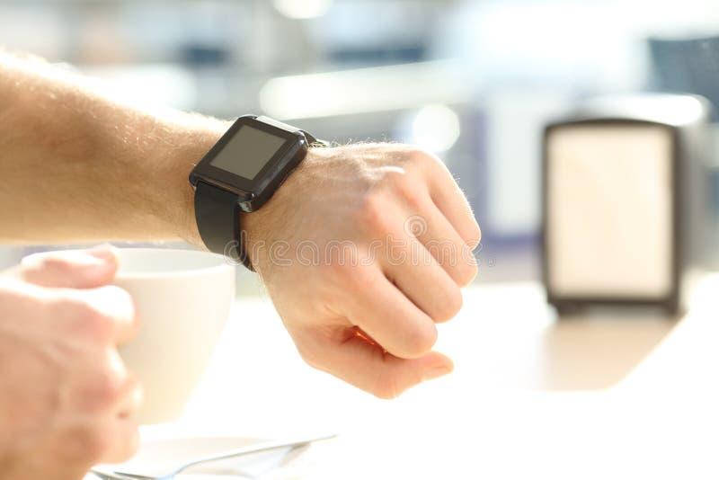 Equipe a mão que consulta um smartwatch em uma barra fotografia de stock royalty free