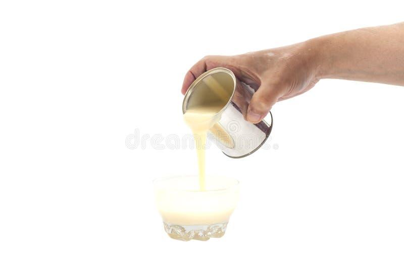 Equipe a mão que derrama o leite condensado em uma bacia fotos de stock royalty free
