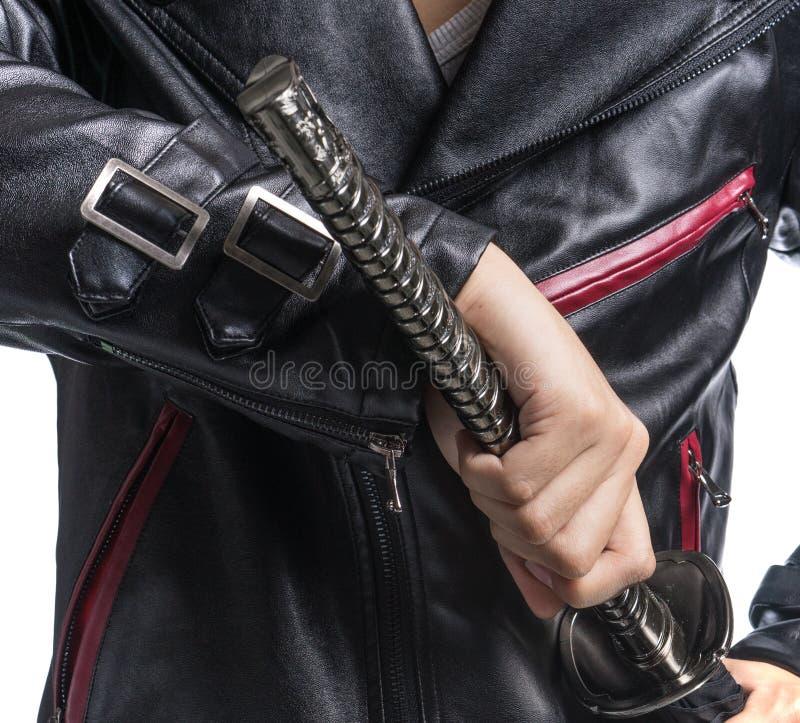 Equipe a mão que guarda a espada do samurai no fundo branco, jaque de couro fotografia de stock royalty free