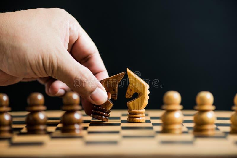 Equipe a mão que guarda preta contra partes de xadrez do cavaleiro branco em ches foto de stock