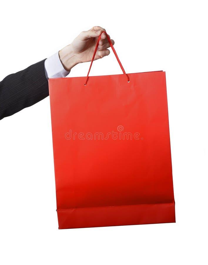 Equipe a mão que leva e que mostra um saco de compras vermelho imagens de stock royalty free