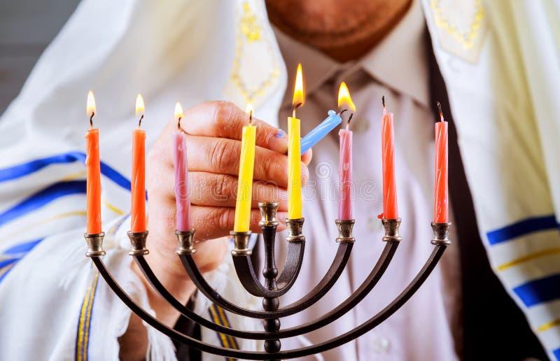 equipe a mão que leve velas na tabela do menorah servida para o Hanukkah imagem de stock