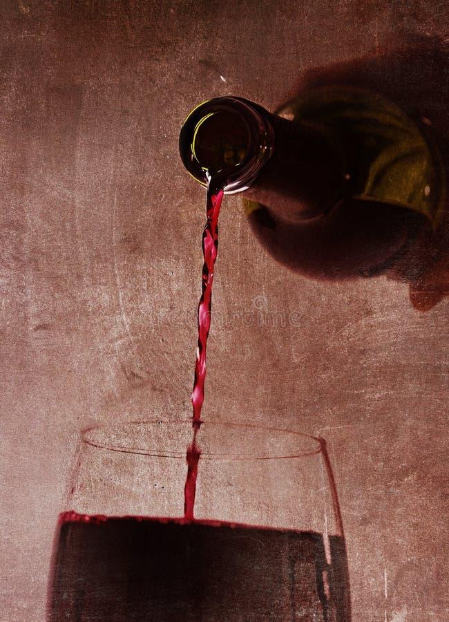 Equipe a mão que mantém o enchimento de derramamento do vinho tinto da garrafa de vidro no fundo dos arty foto de stock