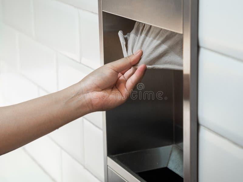 Equipe a mão que puxa um lenço de papel da caixa do tecido no toalete fotos de stock royalty free