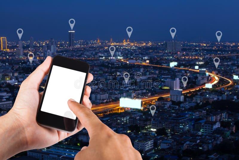 Equipe a mão usando o smartphone que procura o lugar no pino do mapa na parte superior foto de stock