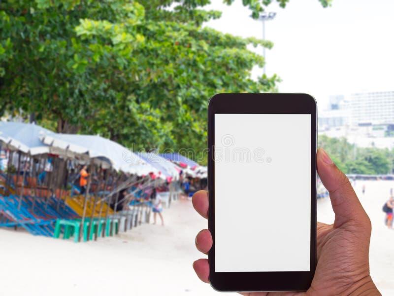 Equipe a mão usando o telefone esperto no fundo da praia imagens de stock royalty free