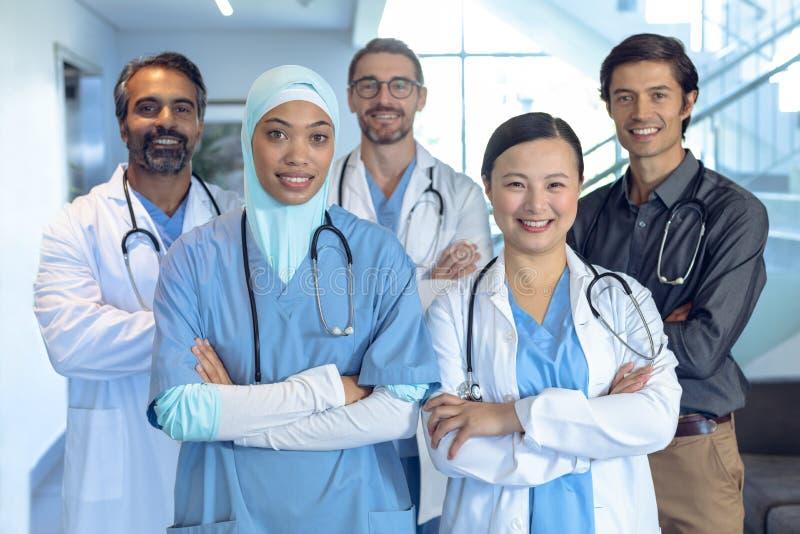 A equipe médica feliz de doutores que estão com braço cruzou-se e que olham a câmera no hospital foto de stock royalty free