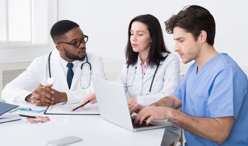 Equipe médica nova que discute relatórios, usando o portátil foto de stock royalty free
