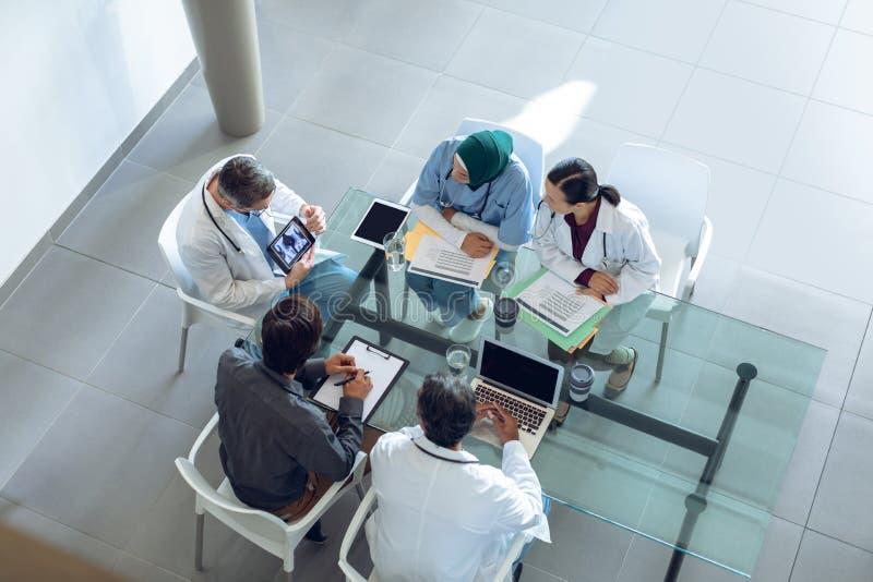 Equipe médica que discute o relatório do raio X sobre a tabuleta digital na tabela no hospital foto de stock royalty free