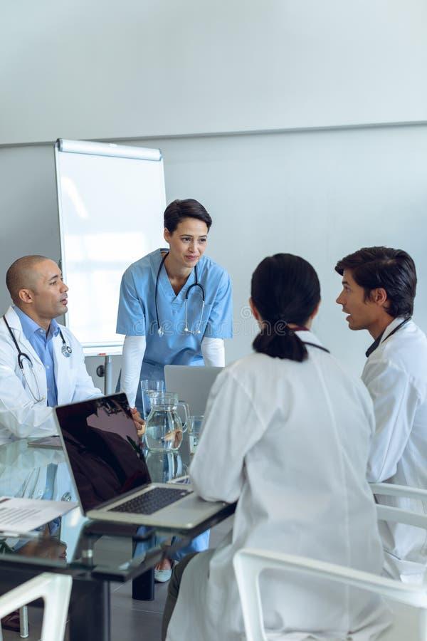 Equipe médica que senta-se e que discute um com o otro na tabela imagem de stock royalty free