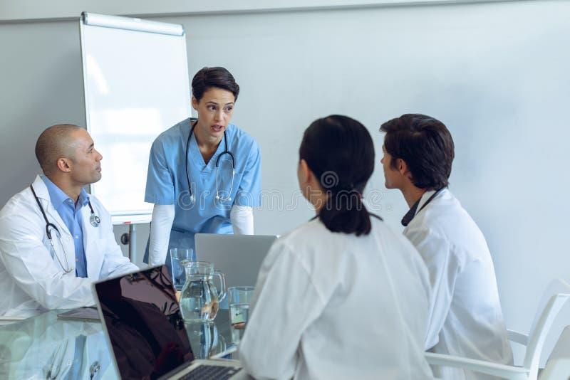 Equipe médica que senta-se e que discute um com o otro na tabela fotografia de stock