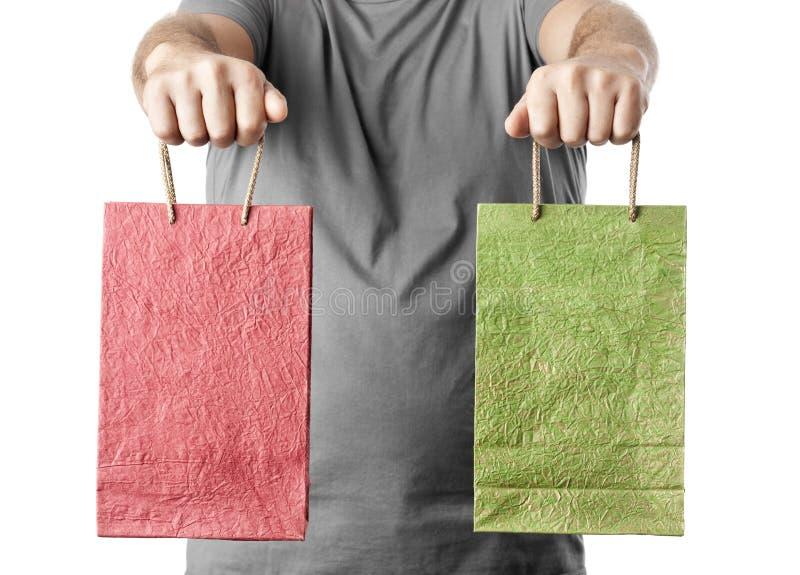 Equipe manter dois sacos de compras isolados no fundo branco imagens de stock royalty free